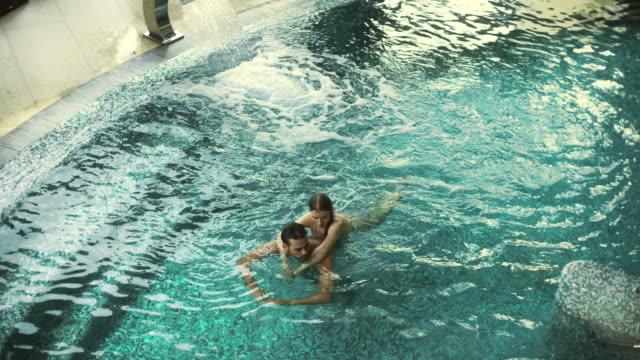 수영장에서 포옹 편안한 커플의 최고 전망. 행복한 남자와 여자는 물에서 휴식 - 스파 온천 스톡 비디오 및 b-롤 화면