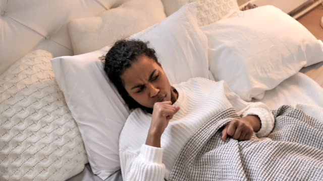 vídeos de stock e filmes b-roll de top view of sick young african girl coughing while sleeping in bed - doença