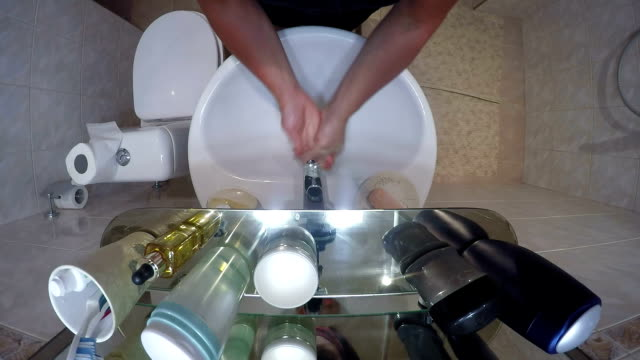Top view of small bathroom interior with sink shower and toilet woman washing hands with liquid soap video