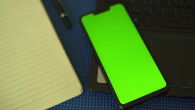 Top view of smartphone chroma key green screen smartphone on laptop