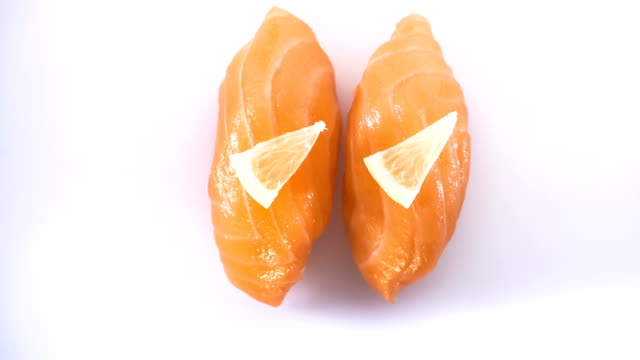 Top view of spinning two salmon sushi with lemon slices.