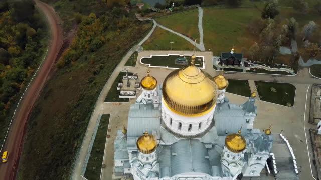 vidéos et rushes de vue de dessus du grand temple chrétien. clip audio. église vue de l'extérieur. l'ancienne église. l'église en pierre de coupoles dorées à l'automne - baptême