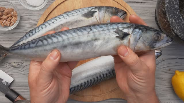 Top view of the male hands placing the round board with three mackerel fishes Top view of the male hands placing the round wooden board with three mackerel fishes on the table fillet stock videos & royalty-free footage