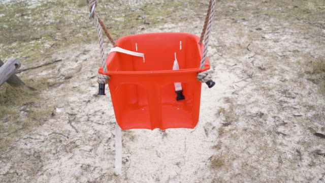 Top view of the orange seat of the swing in Varska Estonia Top view of the orange seat of the swing in Varska Estonia in the playgroung with the rope on the side outdoor play equipment stock videos & royalty-free footage