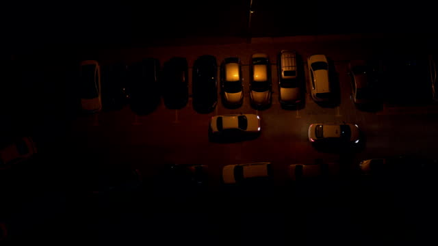 Top view of the parking lot from the roof of a skyscraper at night. Parking by various vehicles in the dark. Top view of the parking lot from the roof of a skyscraper at night. Parking by various color vehicles in the dark. low lighting stock videos & royalty-free footage