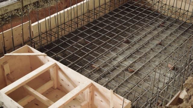 ovanifrån av processen för formsättning av utrymme, byggare är engagerade i byggandet av en struktur av armerad betong - fasta bildbanksvideor och videomaterial från bakom kulisserna