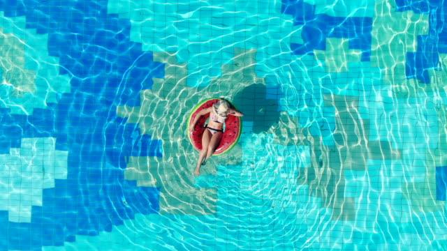 stockvideo's en b-roll-footage met bovenaanzicht van het zwembad met een dame in een zwem ring. zomervakantie concept. - opblaasband