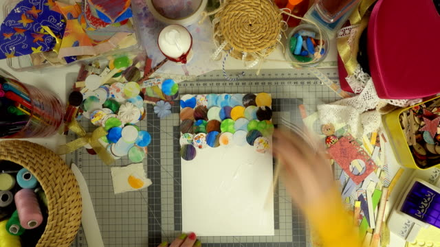 Top view of the work of craftswoman. Time lapse of scrapbooking process.