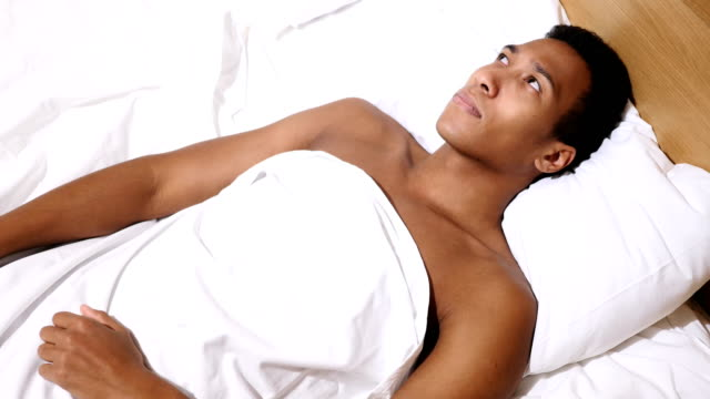 Top View of Thinking Pensive African Man Relaxing in Bed video