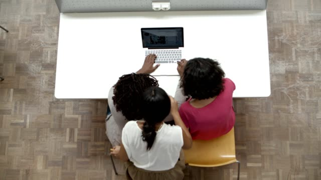 Top view of three women looking at laptop