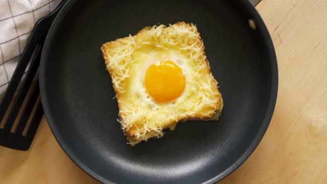 stockvideo's en b-roll-footage met top uitzicht van toast met gebakken ei in pan op houten keuken tafel - geroosterd brood