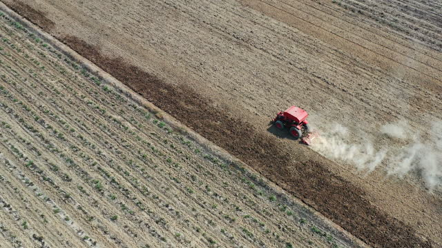 Top view of tractor cutting furrows in farm field for sowing farm Aerial top view of tractor cutting furrows in farm field for sowing farm harrow agricultural equipment stock videos & royalty-free footage