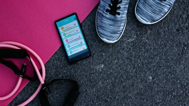 Top view of training accessories and smartphone with fitness application video