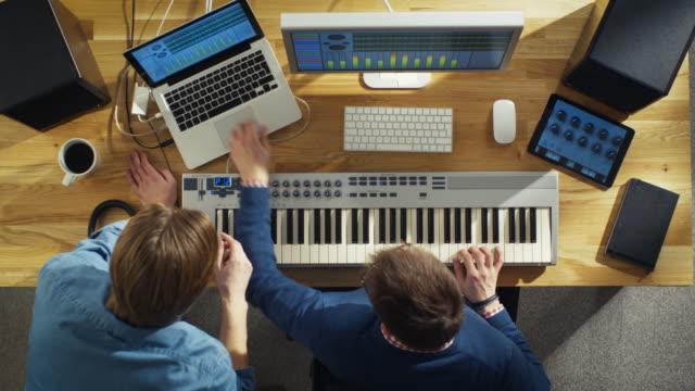 vidéos et rushes de vue de dessus de deux ingénieurs audio travaillant dans leur studio ensoleillé. ils jouent sur un clavier musical et expérimenter avec le son. - synthétiseur
