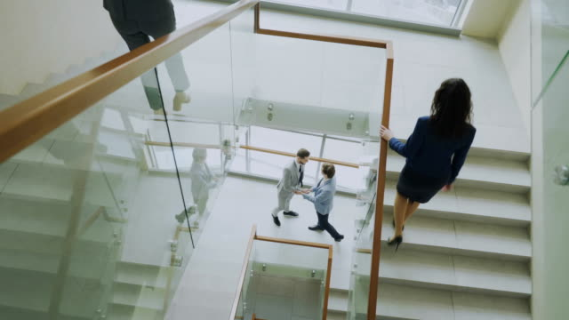 Top view of two businessmen meet at staircase in modern office center and talking while female colleagues walking stairs Top view of two businessmen meet at staircase in modern office center indoors and talking while female colleagues walking stairs lobby stock videos & royalty-free footage