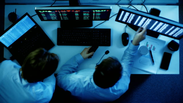 探していると市場を分析、2 つの株式ブローカーの平面図です。彼らの前に 2 つは証券取引所の数値、グラフで監視します。彼らは夜遅くまで作業しています。 ビデオ