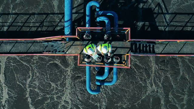 Top view of two wastewater operators working at a wastewater treatment facility video
