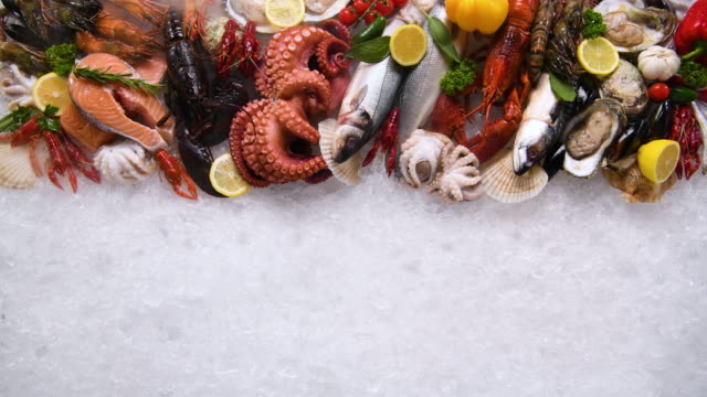 Top view of variety of fresh fish and seafood on ice with dry ice smoke.