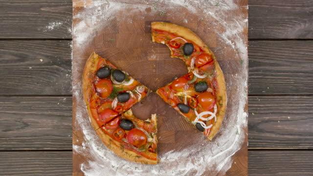 vista dall'alto della pizza vegetariana che mangia su un piatto di legno, animazione stop motion - fetta video stock e b–roll