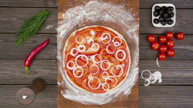 vídeos de stock e filmes b-roll de top view of vegetarian pizza on wooden plate on the table, stop motion animation - pizza