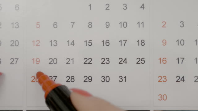 top view of woman hands marking birthday on her calendar agenda with red marker planning surprise party - attività del fine settimana video stock e b–roll