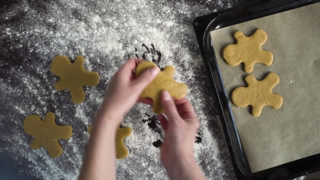 top view of woman hands putting raw gingerbread man cookies on baking tray top view of woman hands putting raw gingerbread man cookies on baking tray. Christmas preparation, homemade food, festive mood gingerbread man stock videos & royalty-free footage