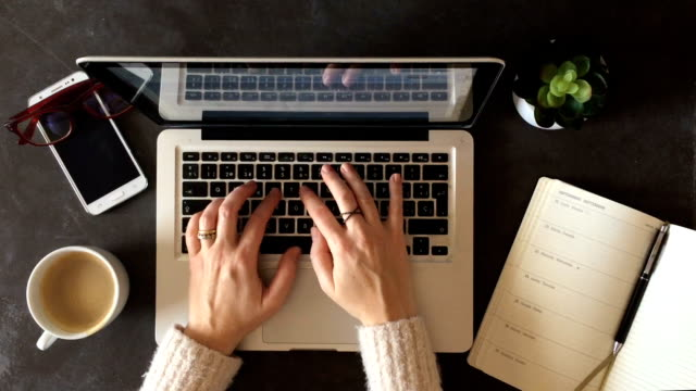 HD Top view of woman hands typing on computer. Smartphone, coffee, glasses and plant on desk.