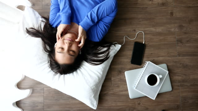 Top view of woman lying down listening music on the wood floor with cup of coffee, Lifestyle concept video