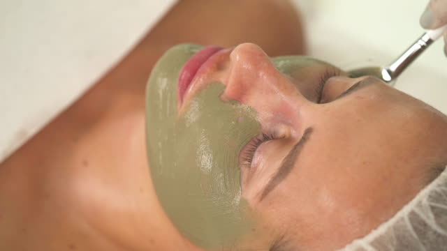 a top view of woman's face with green mask on her left side. a hand in a white rubber glove applies more mask on the right side - facial stock videos & royalty-free footage