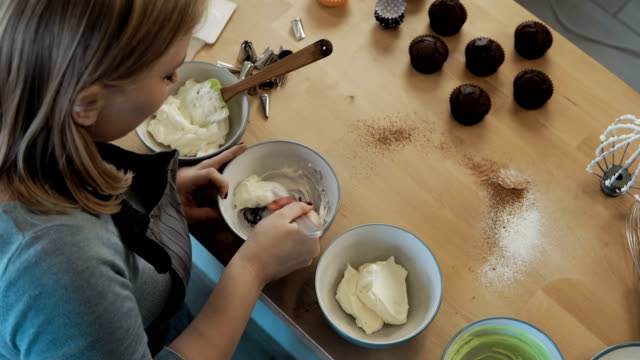 Top view of young beautiful woman mixing the cream for decorating cupcakes. Female cooking in the kitchen video