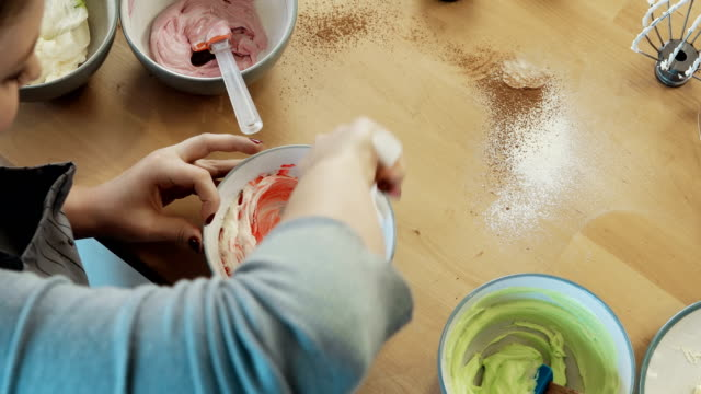 Top view of young blonde woman mixing the cream for decorating and dye in the bowl. Female cooking cupcakes video