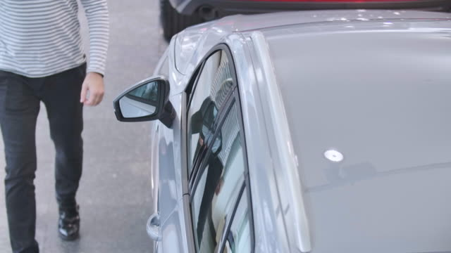 Top view of young Caucasian man opening car door, sitting into salon and closing automobile. Confident owner or lessee getting into vehicle. Car dealership, car business. Cinema 4k footage ProRes HQ. Top view of young Caucasian man opening car door, sitting into salon and closing automobile. Confident owner or lessee getting into vehicle. Car dealership, car business. Cinema 4k footage ProRes HQ. car rental stock videos & royalty-free footage