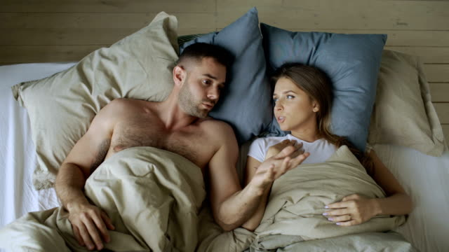 Top view of young couple lying in bed upset and argue each other video