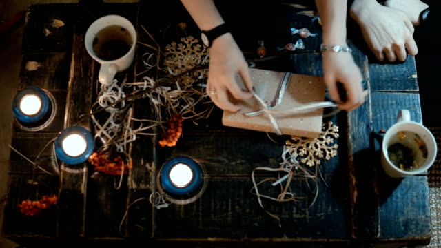 Top view of young couple sitting at the table and drinking tea. Young woman opening the Christmas present what man given video