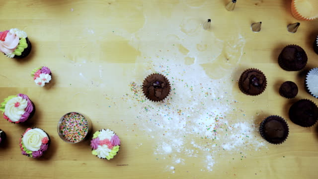 Top view of young female hands decorating the chocolate cupcake or muffin with cream, using pastry bag for this video