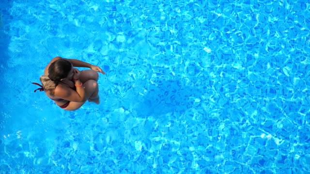 stockvideo's en b-roll-footage met bovenaanzicht van jonge vrouw springen in het zwembad en spatten kristalhelder water. onherkenbaar meisje rusten en plezier op het resort. dame ontspannen tijdens de zomervakantie of vakantie. slow motion close-up - swimmingpool kids