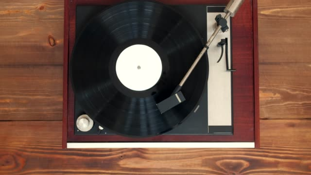 Top view - Old vintage good looking turntable playing music with vinyl on wooden background. 4k Uhd.