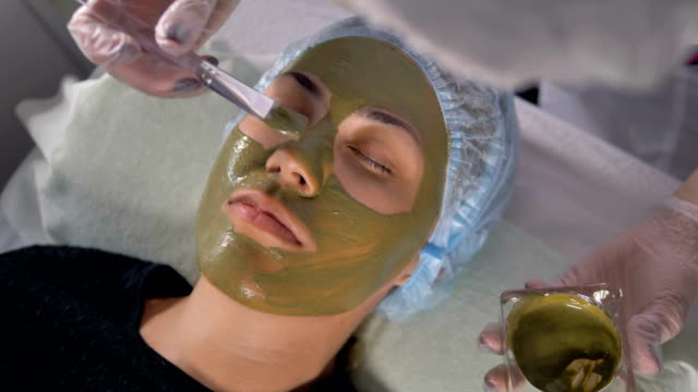 Top view on a female face covered with a green mud mask. video