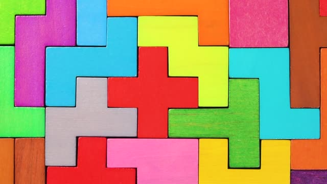 Top view on colorful wooden blocks crumbling on the wooden background. The concept of logical thinking. Concept of decay.