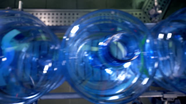 Top view on empty water bottle necks on factory line. video