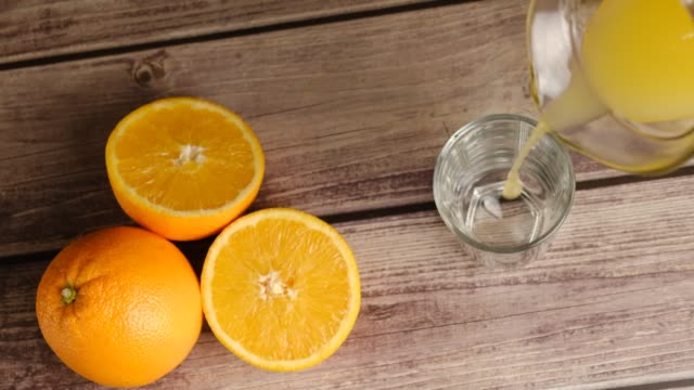 Top view on fresh yellow juice being poured from the pitcher in a tall glass on wooden table with tangerines. Homemade fruit orange juice, soda or lemonade. Organic vitamin drink. Slow motion.