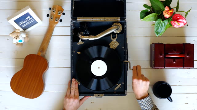 top view on male hands turning on vintage gramophone at white table background. man putting stylus with needle on rotating vinyl record and enjoying classical music. above shot slow motion close up - kompozycja flat lay filmów i materiałów b-roll
