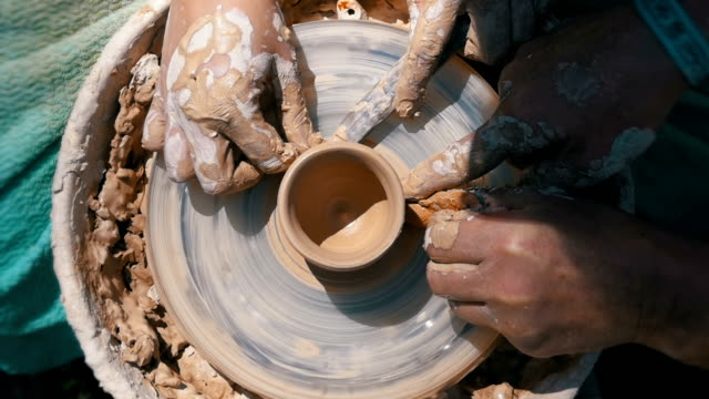 Top view on Potter's Hands Work with Clay on a Potter's Wheel. Slow motion