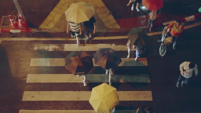 vídeos de stock e filmes b-roll de top view; pedestrian crowd cross the crosswalk on the raining night - guarda chuva