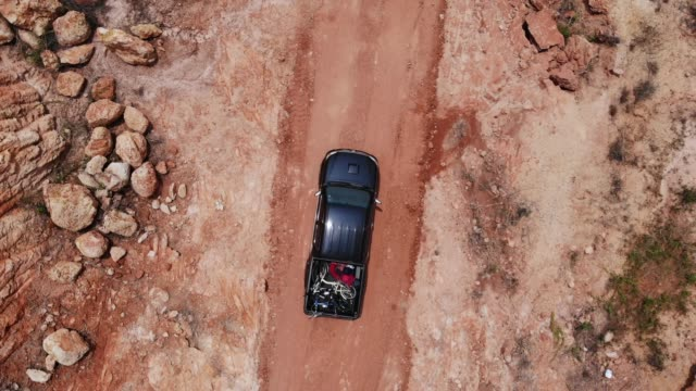 vídeos de stock e filmes b-roll de top view pick up truck off road with load bike - estrada em terra batida
