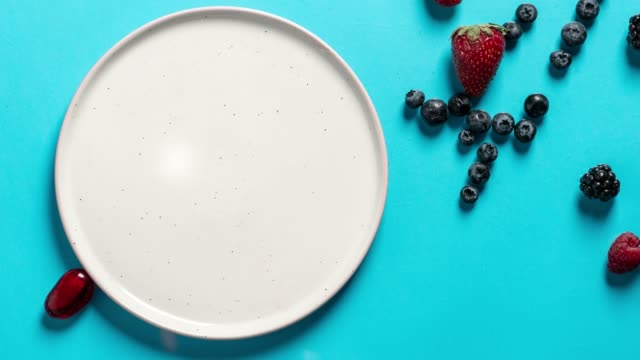 top view plate with variety of forest fruits, berries and hearts on a blue background, stop motion animation - bułgaria filmów i materiałów b-roll