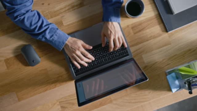 vídeos y material grabado en eventos de stock de tiro giratorio de vista superior: en el empresario de office sentado en el escritorio de madera abre el ordenador portátil y comienza a trabajar bebe café, tipos, escribe correos electrónicos, navega por internet, diseña software - principios