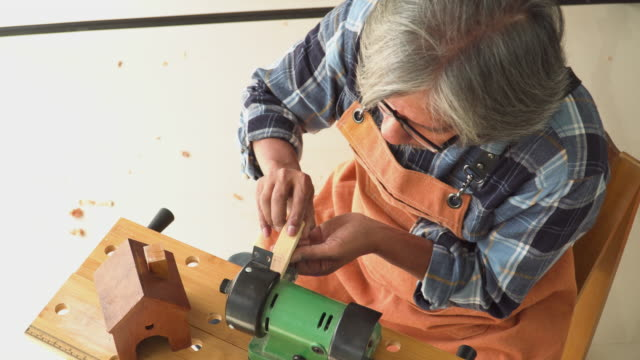 top view: senior carpenter's hand removing wood corners by electric machine in the workshop house
