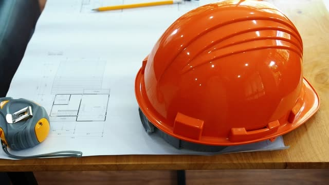 Top view shot of architectural helmet, pencil and dividers on architectural blueprints with panning right tracking.