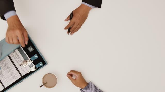 セリングハウスのトップビューショット2人の男性が新しい家の鍵でテーブルの上に握手 - 白い背景コピースペーススタジオショット ビデオ